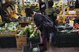 Žena s ochranným rúškom na zabránenie šíreniu nového koronavírusu kupuje zeleninu v obchode v Tokiu.