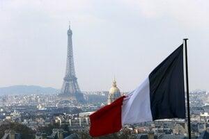 Na archívnej snímke je francúzska vlajka a uprostred v pozadí Eiffelova veža v Paríži. Ilustračná fotografia.