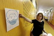 Riaditeľka Základnej školy Tbiliská 4 Zuzana Hirschnerová umiestňuje na stenu chodby s triedami oznam o ochranných opatreniach.
