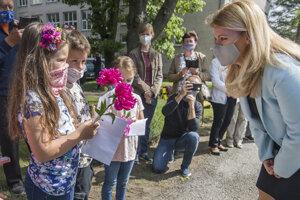 Prezidentka Čaputová (vpravo) dostáva kvety od detí počas navštevy Základnej školy v obci Lozorno.