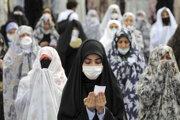 Veriaci v rúškach počas modlitby mimo svätyne v iránskom Teheráne.