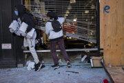 Ľudia si vynášajú tovar počas rabovania obchodu v newyorskej štvrti Chelsea.