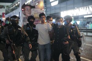 Policajti zadržujú muža počas protestu pri príležitosti prvého výročia od začiatku prodemokratických demonštrácií v Hongkongu.