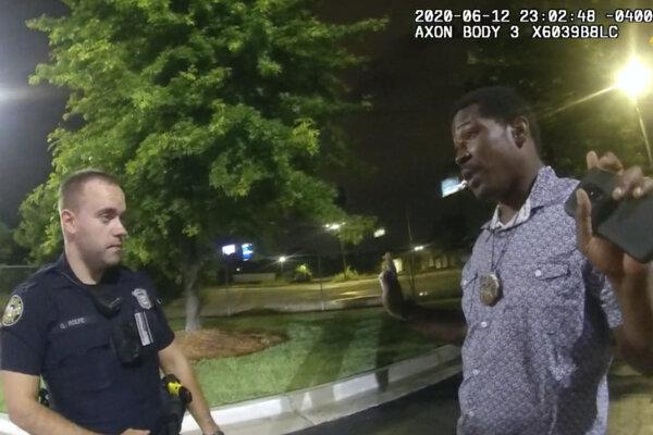 Rayshard Brooks sa rozpráva s policajtom Garrettom Rolfeom.