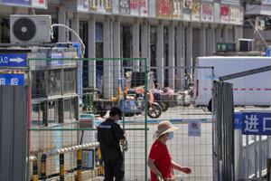 Bezpečnostný pracovník uzamyká reťazou oplotenie pred hlavným vchodom veľkoobchodného trhu s rybami a inými morskými živočíchmi, ktorý je zavretý pre inšpekciu v čínskom Pekingu.
