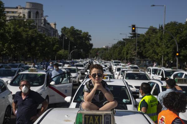Chlapec sedí na streche taxíka počas protestu taxikárov v centre Madridu.
