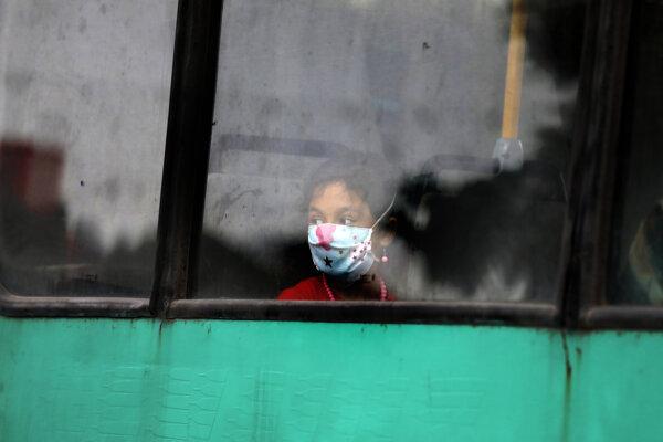 Dievča s ochranným rúškom cestuje verejnou dopravou v iránskom meste Zanjan.