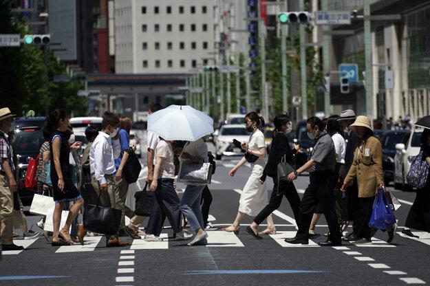 Ľudia kráčajú cez križovatku na ulici v Tokiu.