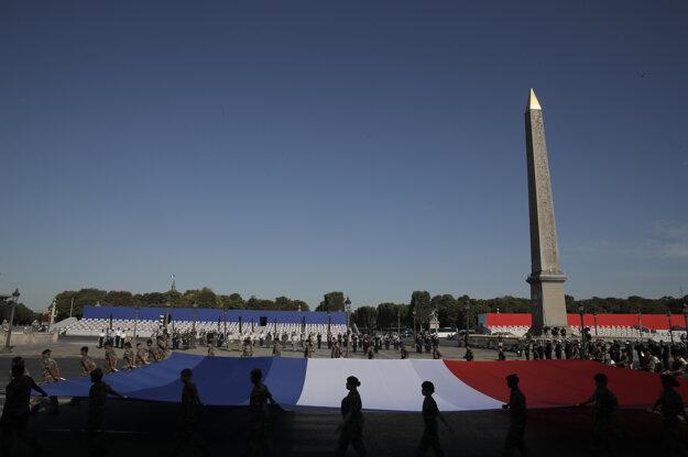 Vojaci držia francúzsku vlajku počas nácviku na utorňajšiu prehliadku v Deň dobytia Bastily, v pondelok 13. júla na námestí Place de la Concorde.