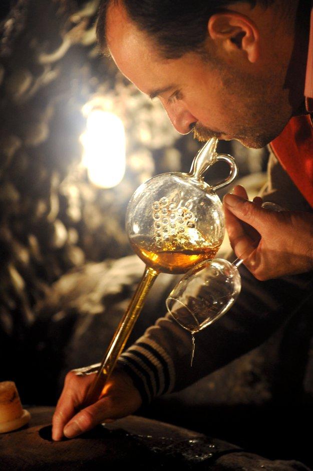 Naťahovanie vína heverom v pivnici.