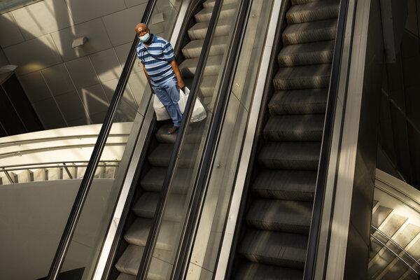 Muž s ochranným rúškom na eskalátore v Bruseli.