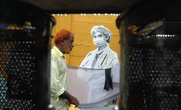 Muž prechádza okolo nástennej maľby na počesť zdravotníkov bojujúcich proti koronavírusu neďaleko vlakovej stanice v indickom Bombaji.