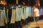 Demonštrant pred políciou na proteste proti výsledkom prezidentských volieb v bieloruskej metropole Minsk.