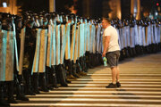 Demonštrant sa rozpráva s policajtmi, ktorí blokujú cestu počas protestov proti výsledkom prezidentských volieb v bieloruskej metropole Minsk v nedeľu 9. augusta 2020.