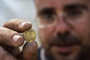 Izraelský archeológ Shahar Krispin ukazuje jednu zo zlatých mincí.