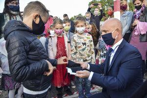 Minister školstva, vedy, výskumu a športu SR Branislav Gröhling rozdáva žiakom ochranné rúška