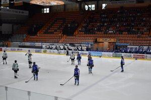 Smutná realita na zimnom štadióne. Hŕstka ľudí na tribúnach a protestné búchanie hráčov hokejkami o ľad.