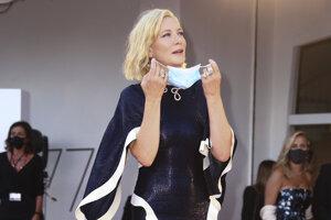 Predsedníčka poroty Cate Blanchett v šatách, ktoré si na slávnostnú príležitosť obliekla po druhý raz, si nasadzuje rúško.