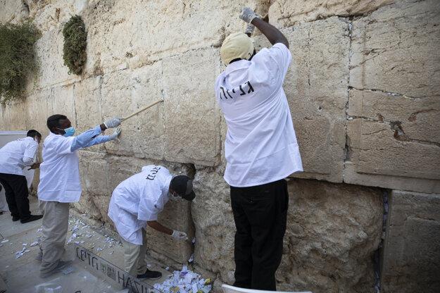 Koronavírus vo svete: Pracovníci odstraňujú modlitebné lístky návštevníkov medzi kameňmi z Múru nárekov v Jeruzaleme 16. septembra 2020.