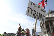 Toto je tyrania. Transparent s takýmto nápisom drží jeden z účastníkov protestov proti opatreniam na Trafalgarskom námestí v Londýne.
