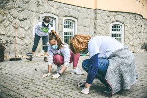 Dobrovoľníčky čístia dlažbu na dvore autistického centra Andreas.