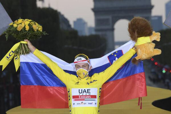 Tadej Pogačar pózuje v žltom drese a so slovinskou vlajkou.