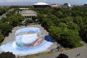 Americko-kubánsky umelec Jorge Rodriguez-Gerada maľuje zdravotného pracovníka na veľkej ploche v newyorskej štvrti Queens v stredu 27. mája 2020.