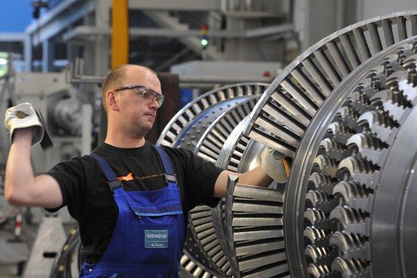 Na archívnej snímke z mája 2009 robotník na montážnej linke pre turbíny v továrni Siemens Energy v Görtlizi.