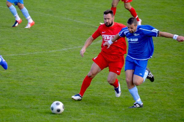 Domáci Pavol Bulko (v červenom) v súboji o loptu s Dáriusom Jančovičom v zápase Veľké Bierovce/Opatovce - Záblatie 2:2.