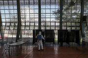 Pracovník dezinfikuje volebnú miestnosť v Santiagu v Čile.