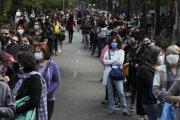 Ľudia stoja v dlhých radoch pred volebnými miestnosťami v Santiagu počas referenda o novej ústave v Čile v nedeľu 25. októbra 2020.