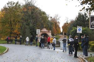 Ľudia stoja v rade na testovanie pri amfiteátri v Košiciach.