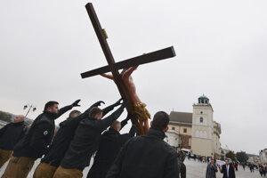 Stúpenci krajnej pravice kráčajú s krížom počas pochodu proti LGBTI komunite vo Varšave.