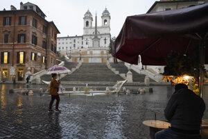 Žena s ochranným rúškom kráča popri Španielskych schodoch v Ríme.