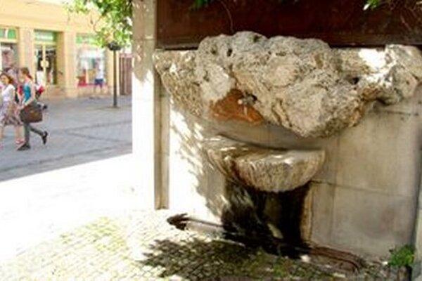 Pitná fontánka na pešej zóne bez koníkov a mreže.