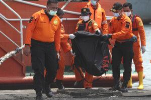Záchranári nesú zakryté trosky, ktoré vytiahli z vôd Jávskeho mora z havarovaného lietadla indonézskej spoločnosti Sriwijaya Air.