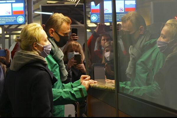 Ruský opozičný líder Alexej Navaľnyj (zelená bunda) a jeho manželka Julija počas pasovej kontroly na moskovskom letisku Šeremeťjevo.
