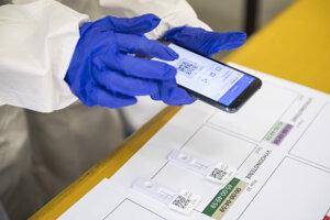 Zdravotnícky pracovník skenuje QR kódy pacientov počas otvorenia odberného miesta MČ Petržalka na Ekonomickej Univerzite.