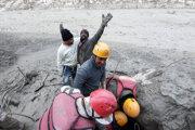 Muž sa teší po tom, čo ho  vytiahli spod zeme počas záchranných prác po povodni v Indii zo začiatku februára.