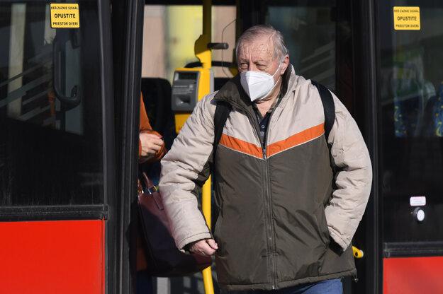 Cestujúci s respirátorom stojí na zastávke MHD v Prešove.