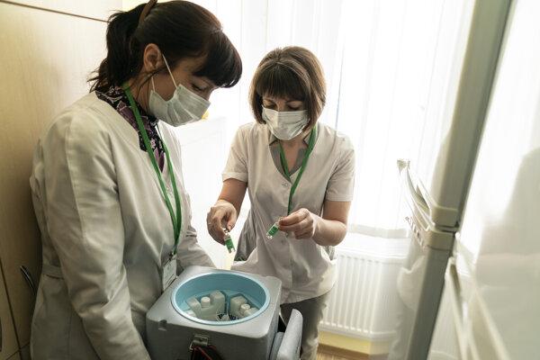 Zdravotné sestry ukladajú vakcíny od spoločnosti AstraZeneca do boxu v ukrajinskom meste Selydove.