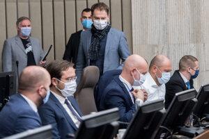 Premiér Igor Matovič prechádza okolo ministrov za SaS Richarda Sulíka a Branislava Gröhlinga počas rokovania vlády.