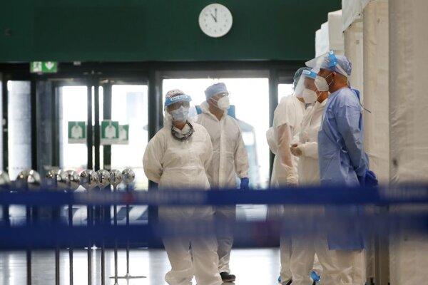 Talianski zdravotníci v ochranných odevoch a s ochrannými štítmi na zabránenie šíreniu nového koronavírusu čakajú na pasažierov prichádzajúcich z rizikových stredomorských krajín počas testovania na ochorenie COVID-19 na letisku Malpensa v Miláne.