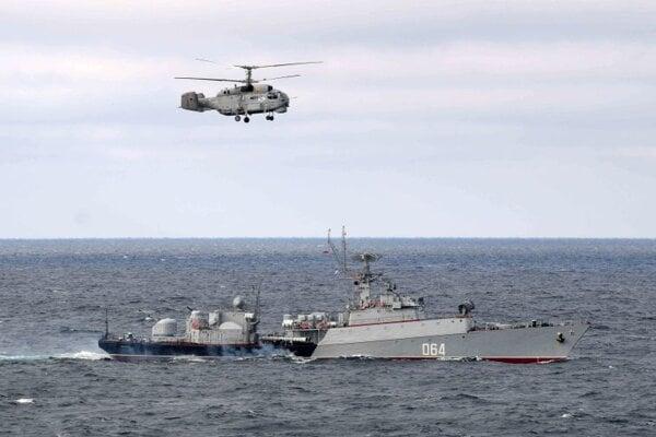 Ruský armádny vrtuľník letí nad ruskou vojnovou loďou počas manévrov v oblasti Čierneho mora.