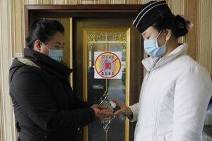 Pracovníčka obsluhly reštaurácie v Pchjongjangu aplikuje dezinfekciu zákazníčke pri vstupe.