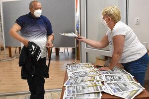 Pred vstupom do čakárne dostali ľudia časopisy.