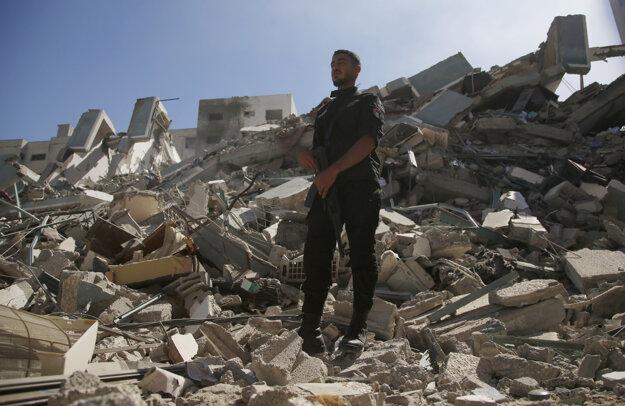 Muž prechádza po troskách zrútenej budovy v Gaze, v ktorej mali svoje kancelárie viaceré zahraničné médiá.