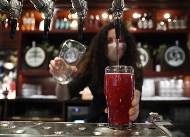 Čašníčka čapuje prvý alkoholický nápoj - cider - v pube Shakespeare's Head v Londýne, v ktorom po prvý raz od posledného lockdownu privítali zákazníkov vo vnútorných priestoroch