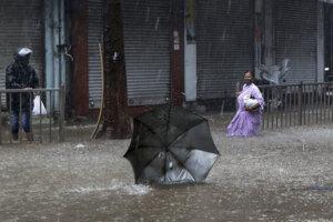 Žena sa brodí po zaplavenej ulici po tom, ako jej uletel dáždnik počas prudkého dažďa a vetra v indickom Bombaji 17. mája 2021.