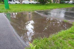 Žiaci a učitelia musia mláky obchádzať po mokre tráve ale cez parkovisko.